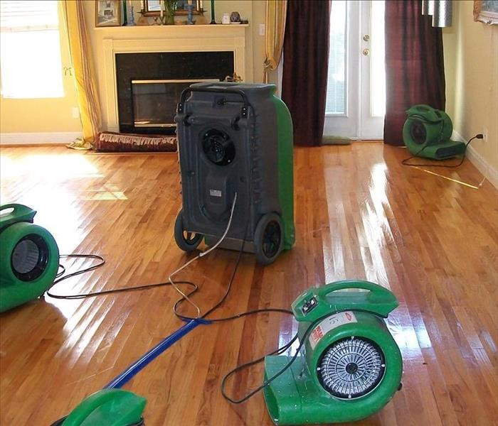 view of green equipment drying a hardwood floor with a fireplace in the background, slight cupping of the edges